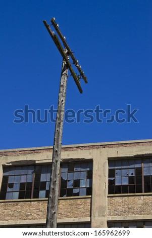 Urban Automotive Blight Telephone Pole - Abandoned Automotive Factory - Worn, Broken and Forgotten - stock photo