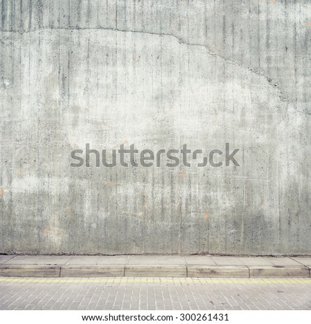 Urban background. Grunge obsolete concrete wall and pavement. - stock photo