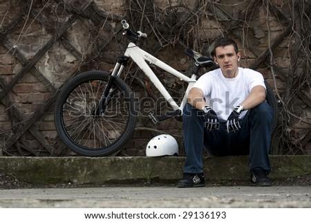 Urban bike rider resting next to his bike. - stock photo