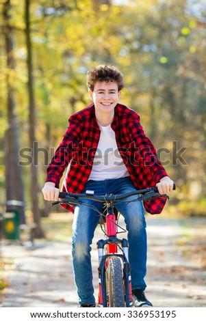 Urban biking - teenage boy riding bike in city park  - stock photo