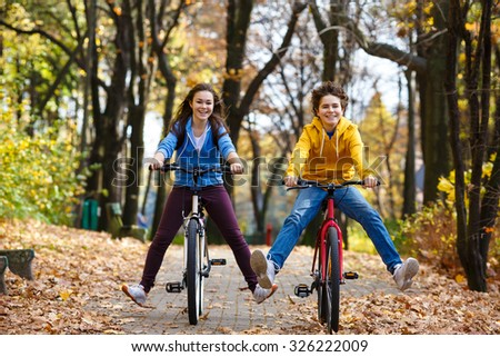 Urban biking - teens riding bikes in city park