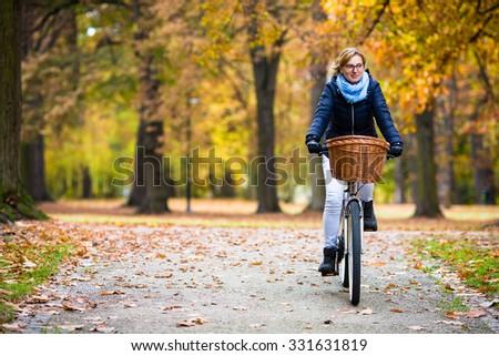Urban biking - woman riding bike in city park  - stock photo