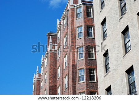 urban brick apartment buildings from below with blue sky - stock photo