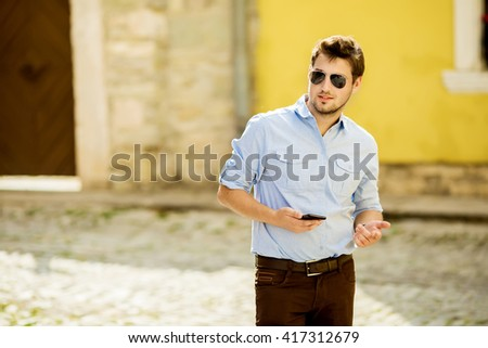 Urban business man talking on smart phone at walking. Handsome male model in his 20s. - stock photo