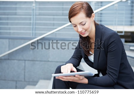 Urban business woman sitting with tablet computer on stairs - stock photo
