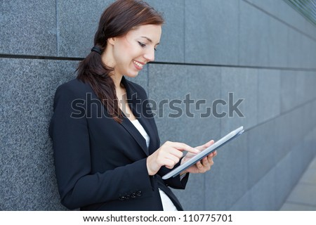 Urban business woman using tablet computer while leaning on wall - stock photo