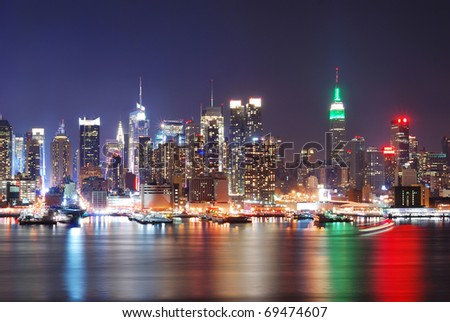 Urban city night scene. Empire State Building, New York City with Manhattan Skyline at night panorama over Hudson River with reflection.