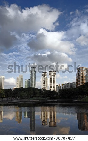 Urban city skyline of Kuala Lumpur city centre with dramatic clouds and reflection of buildings in the lake. Kuala Lumpur is the capital of Malaysia. - stock photo