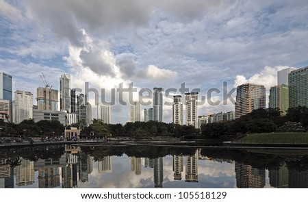Urban city skyline of Kuala Lumpur city centre with reflection in the KLCC lake.
