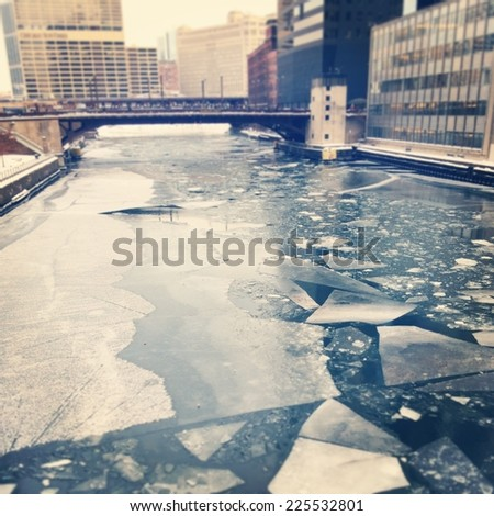 Urban city with semi frozen pond with ice shards floating on the right. - stock photo