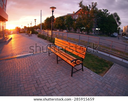 Urban cityscape with benches and lanterns in the evening at sunset with wide angle fisheye lens and distortion view - stock photo