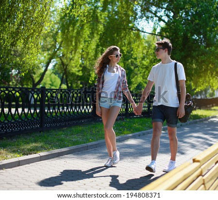 Urban couple teens in love walking in the summer park - stock photo