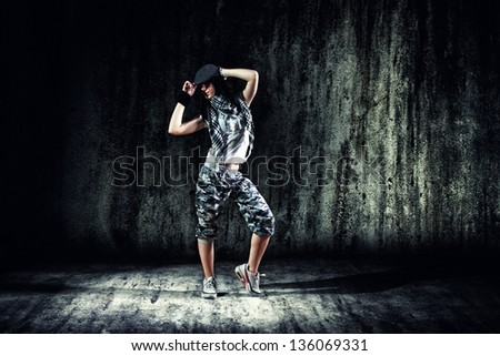 urban dancer with grunge concrete wall background texture jumping and dancing with hoodie