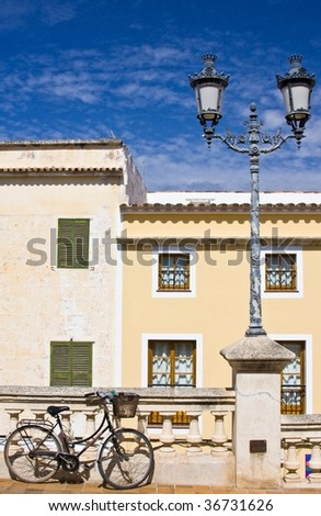 Urban detail of bicycle and lamppost with blue sky - stock photo