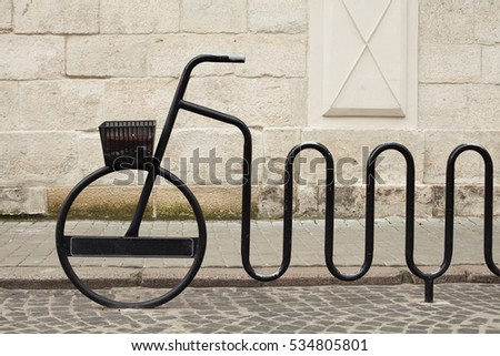Urban environment, ecological transportation concept. Garbage container on metal bicycle installation in old city center of European capital. Minimalism style. Outdoor shot