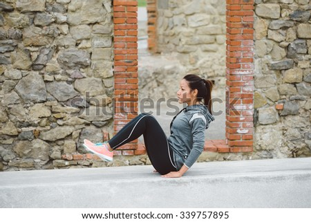 Urban fitness woman doing crunches exercise workout outdoor. Core training and healthy lifestyle concept.