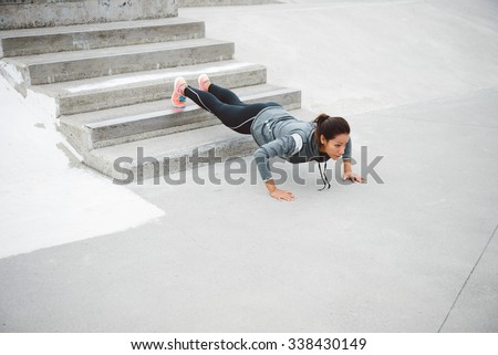 Urban fitness woman workout doing feet elevated push ups and exercising outdoor. Motivated female athlete training hard. - stock photo