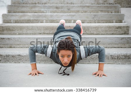 Urban fitness woman workout doing feet elevated push ups on urban park stairs. Motivated female athlete training hard. - stock photo