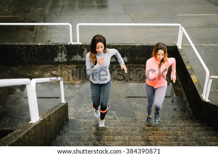 Urban fitness women running and climbing stairs for legs power and strength training. Female athletes working out outdoor in rainy winter day. - stock photo