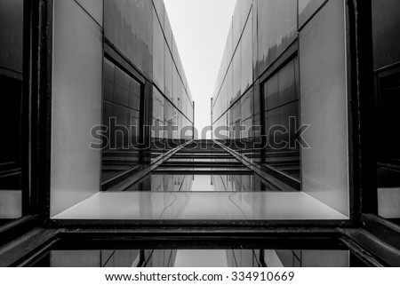 Urban Geometry, looking up to glass building. Modern architecture, glass and steel. Abstract architectural design. Inspirational, artistic image. Industrial design. .Modern building. Black and white. - stock photo