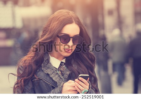 Urban girl writing a message. - stock photo