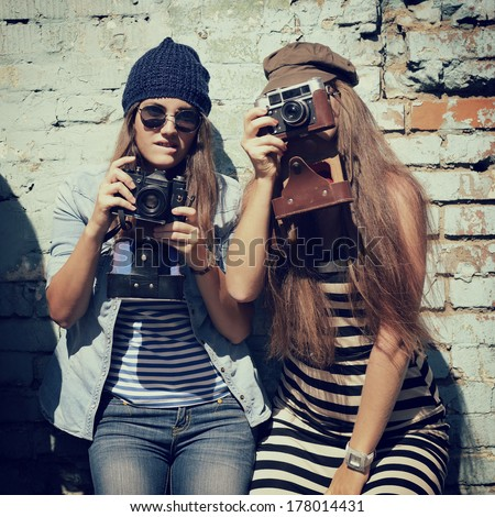 urban girls have fun with vintage photo cameras outdoor near grunge wall, image toned - stock photo