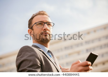Urban guy / businessman with a cellphone outdoors. - stock photo