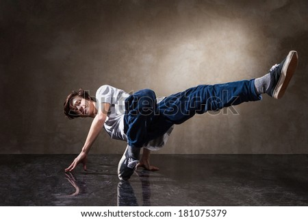 urban hip hop dancer with grunge concrete wall background texture jumping and dancing - stock photo
