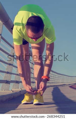 Urban jogger tying his running shoes on a big bridge.