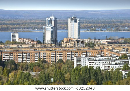 Urban landscape. Typical residential area on the riverbank. The view from the heights in the background high-rise apartment building. Russia.
