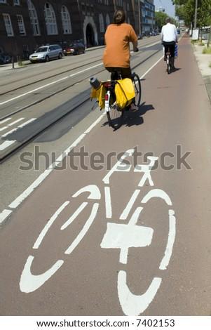 urban lifestyle: couple biking in Amsterdam - stock photo