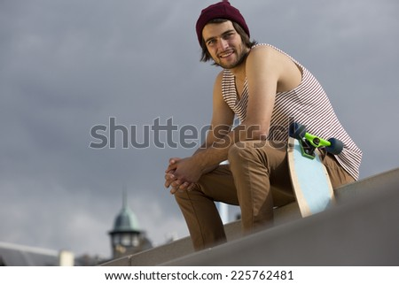 Urban lifestyle portrait of a streetwise skateboarder, sitting on concrete steps - stock photo