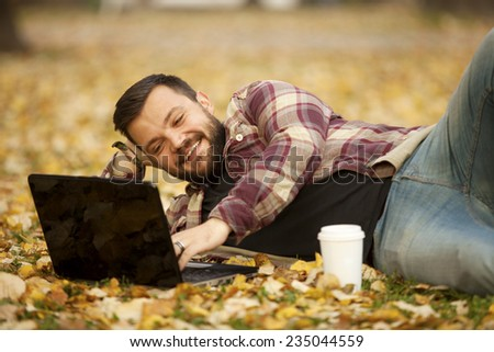 Urban Man Laying Down In Autumn Falling Leaves Using Laptop Computer Outdoor - stock photo