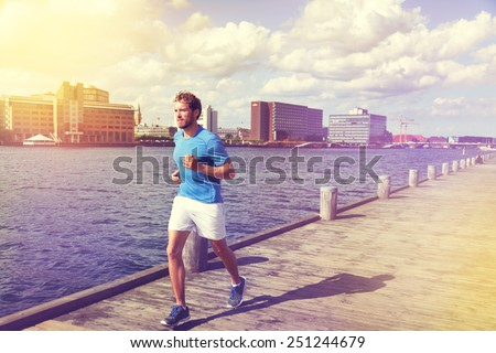 Urban man runner running in Copenhagen city, Denmark. Danish male adult jogging in Bryggen, Copenhagen, Scandinavian Europe. - stock photo