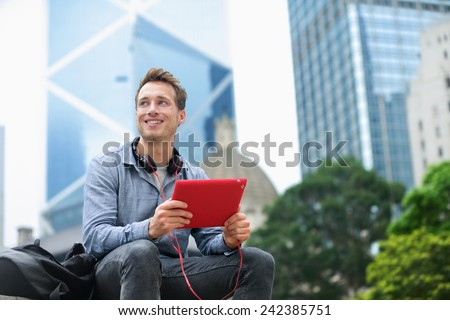 Urban man using tablet computer sitting in Hong Kong outside using app on 4g wireless device wearing headphones. Casual young urban professional male in his late 20s. Hong Kong Central. - stock photo