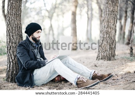 Urban man work on computer at the forest - stock photo