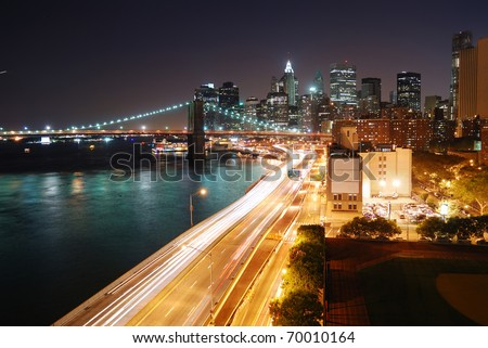 Urban New York City Manhattan skyline and Brooklyn Bridge with skyscrapers over Hudson River illuminated with lights and busy traffic at dusk after sunset. - stock photo