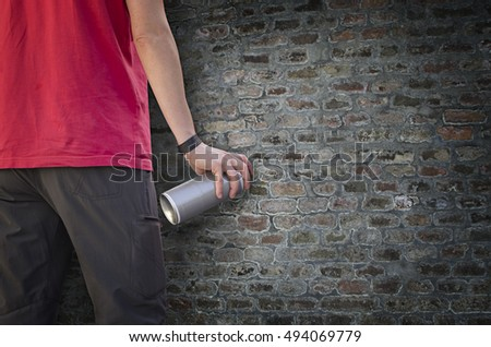 Urban painter holding a graffiti spray can in front of a dark wall