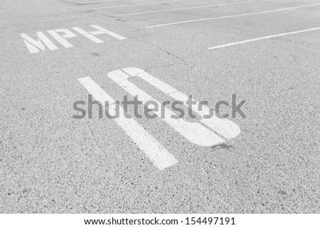 Urban parking lot speed limit road markings.Textured asphalt,empty parking spaces,white dividing lines.10 mph speed limit in painted white letters on ground.Perspective view.Black and white photo - stock photo
