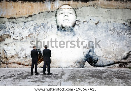Urban people looking at a dilapidated paintwork of a peaceful meditating man on a weathered concrete wall for the concept of urban concrete stress. - stock photo