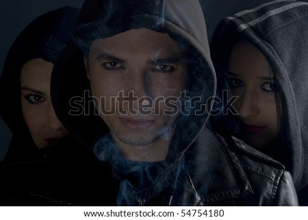 Urban people street in black hoods standing in darkness  with smoke around them and looking you.man in front and two women behind him - stock photo
