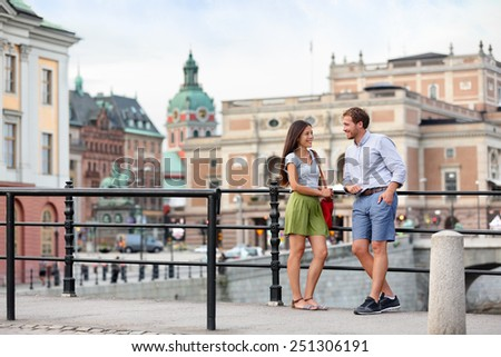 Urban people street lifestyle - couple of tourists on travel or smart casual modern young professionals talking in Stockholm city, Sweden. - stock photo