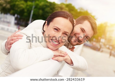 urban photo of smiley young couple in love looking at camera - stock photo