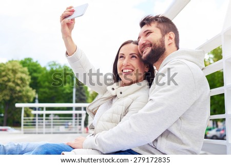 urban photo of smiley young couple sitting and taking a selfie - stock photo