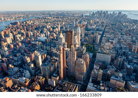 Urban photography of Manhattan showcasing New York cityscape and its buildings and skyscrapers: Midtown, Chelsea, Lower Manhattan, East Village, Financial District and Brooklyn in the distance. - stock photo