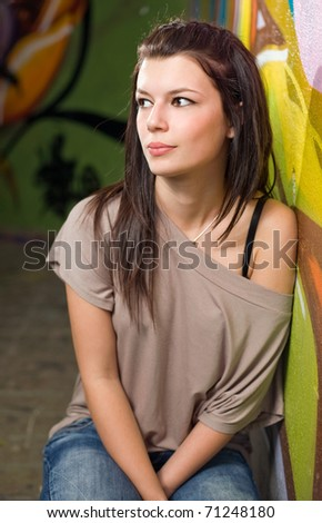 Urban portrait of beautiful young brunette posing in front of graffiti.