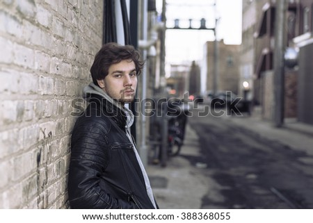 urban portrait of young man posing in alleyway, leaning on brick wall.