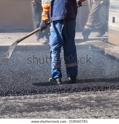 Urban road under construction, asphalting in progress, worker with a shovel in blue uniform - stock photo