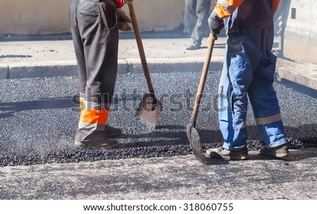 Urban road under construction, asphalting in progress, workers with shovels  - stock photo