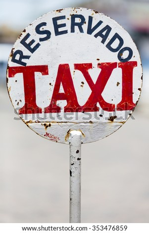 Urban rusty metal sign in Colonia Del Sacramento saying Taxi Parking Only with blurred background, Uruguay - stock photo